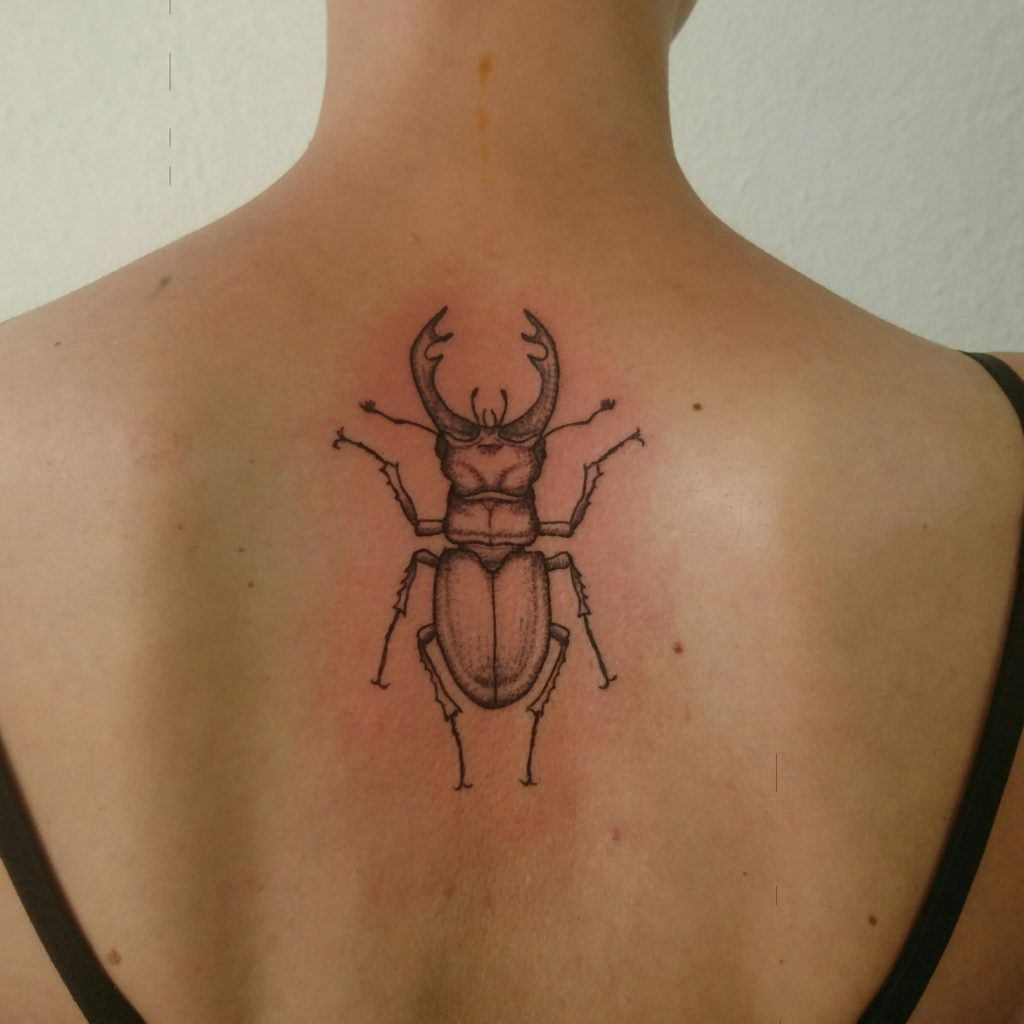 stag beetle tattoo on upper back. line- and dotwork