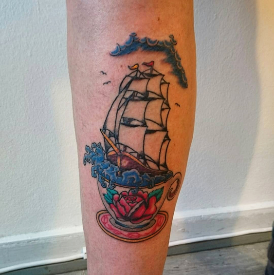 Colorful tattoo of a ship sailing in a cup.