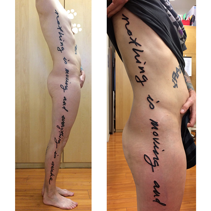 Large text along the whole side of the body, tattoed in black