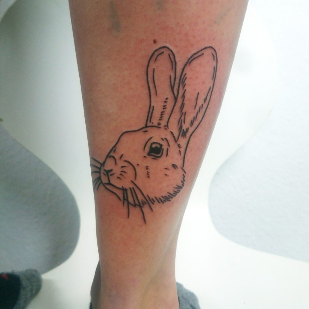 Tattoo of bunny head on lower leg in lineworktattoo and woodcuttattoo style