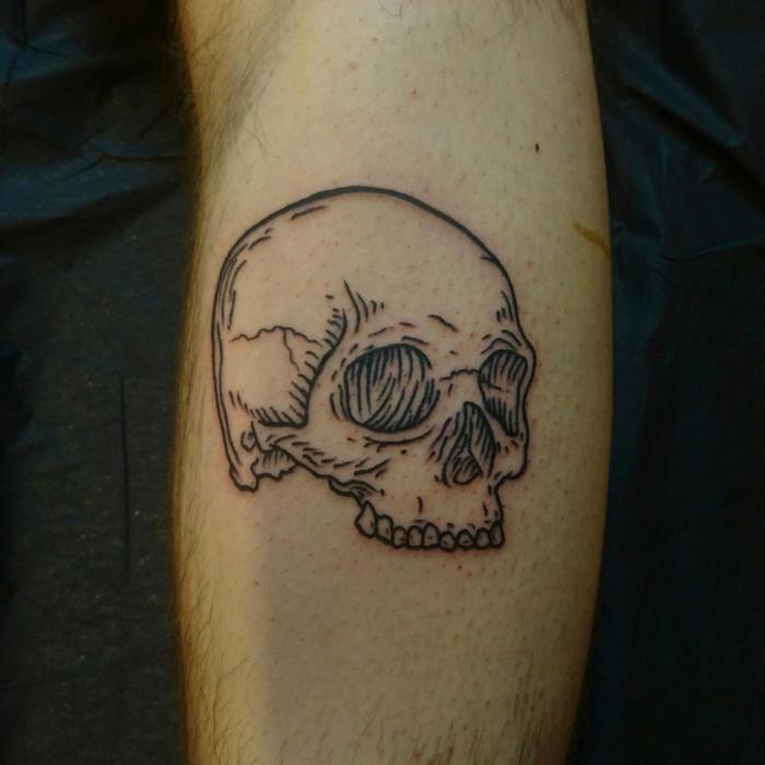 Black tattoo of a skull in lineworktattoo and woodcuttattoo style