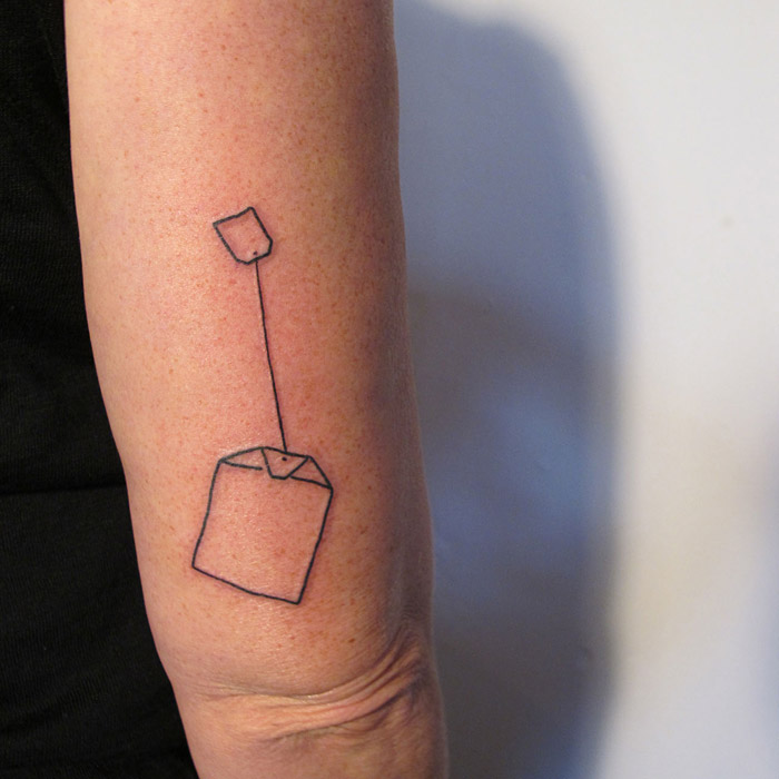 Small tattoo of teabag. Black linework.